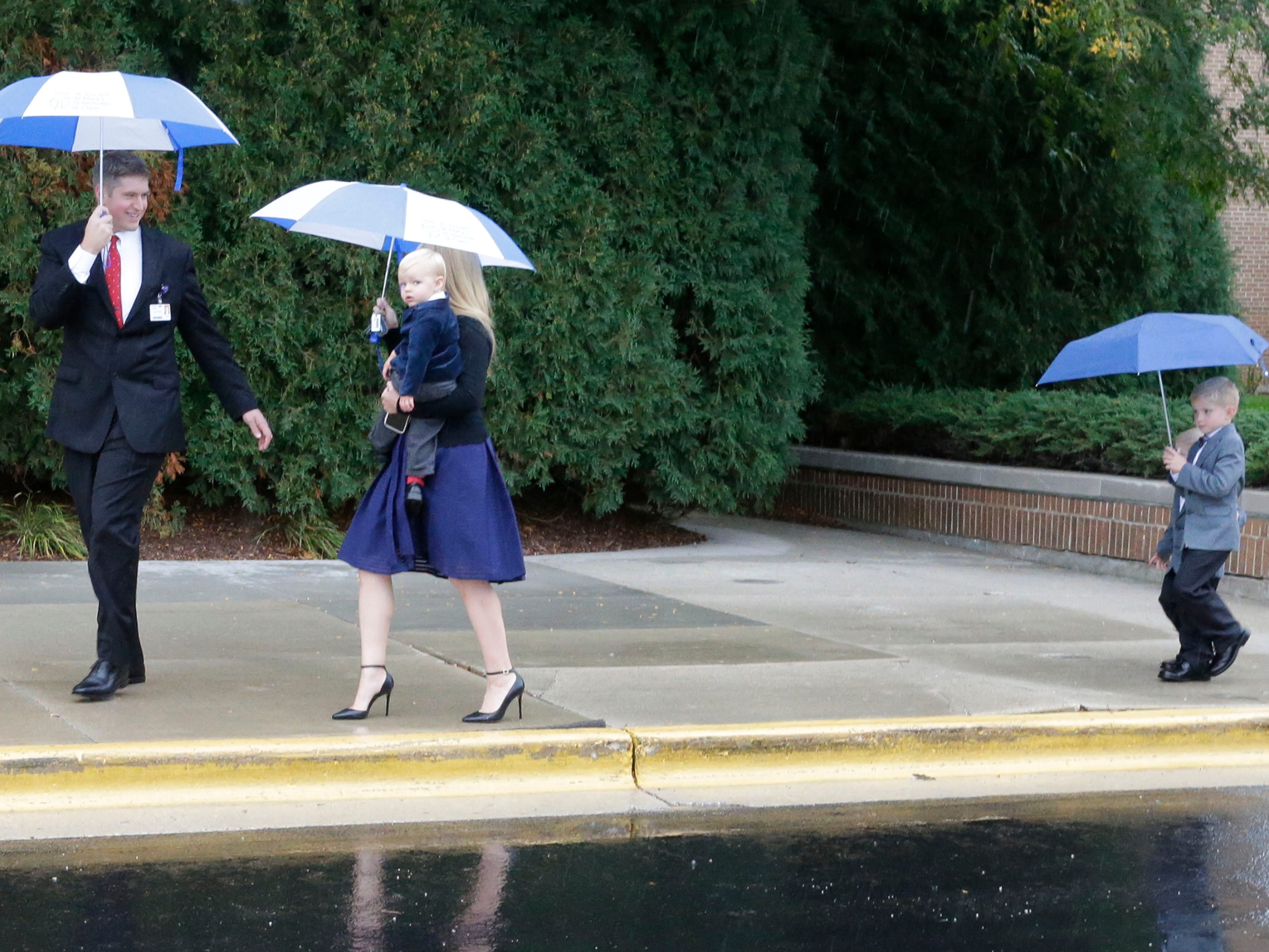 HSHS St. Nicholas Hospital new CEO Justin Selle, left, walks with his family under umbrellas as they arrive to a Mass of Celebration at the facility, Wednesday, September 19, 2018, in Sheboygan, Wis. Selle was officially installed as the new President and CEO of the hospital.