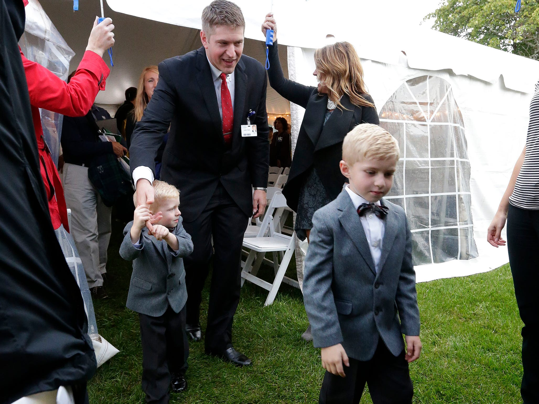 The family of HSHS St. Nicholas Hospital CEO Justin Selle walk under protection of umbrellas as they arrive for the Mass of Celebration, Wednesday, September 19, 2018, in Sheboygan, Wis.