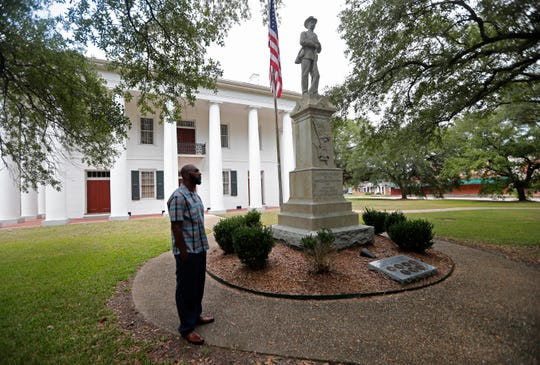 In this Aug. 1, 2018 photo, Ronnie Anderson, an African-American man charged with possession of a firearm by a convicted felon, waits next to a confederate statue on the lawn of the East Feliciana Parish Courthouse in Clinton, La. Anderson is asking for his case to be moved to another location because the courthouse where he's being tried has a Confederate monument in front of it. (AP Photo/Gerald Herbert)
