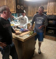 Chris Mazziotti (right) helped prepare meals as part of his stay at Don Dougherty's house in Sioux Falls. Mazziotti caddies for Paul Goydos.