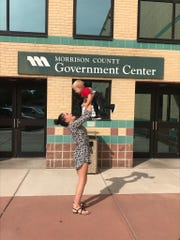 Amanda Weber with her youngest child in front of the Morrison County courthouse in Little Falls.