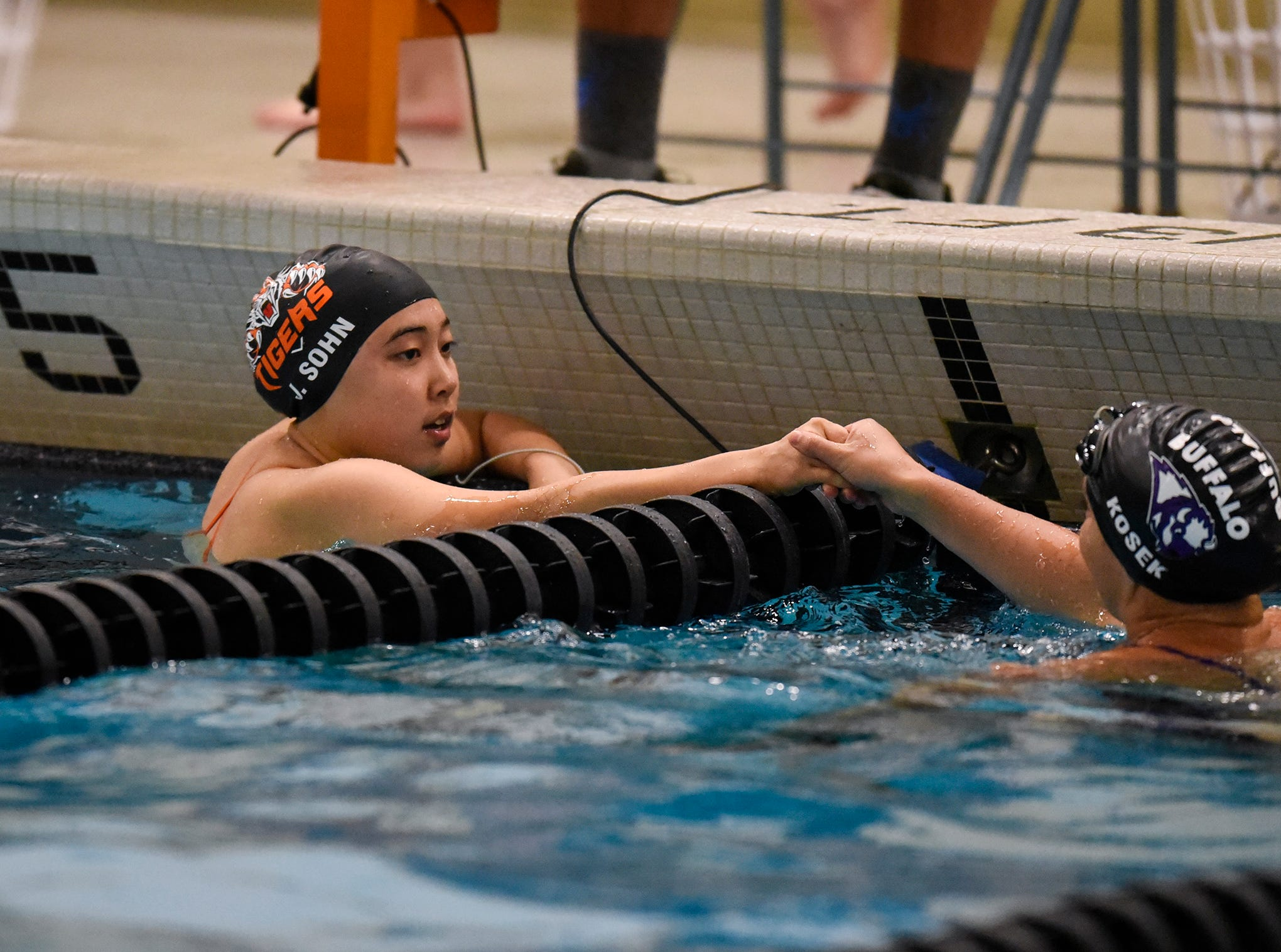 Jeeho Sohn shares a handshake with her opponent following her swim during the Tuesday, Sept. 18 meet against Buffalo at Tech High School in St. Cloud.