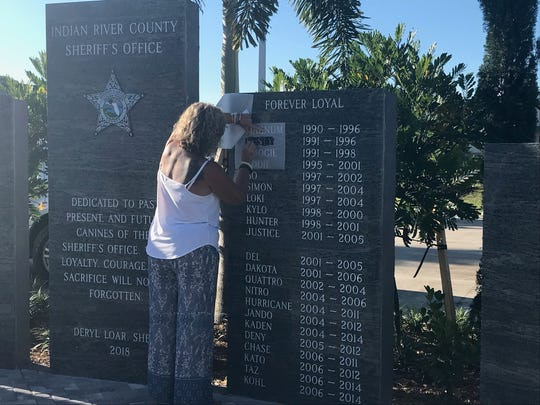 Recently retired deputy Roberta Baker traces the name of her golden retriever, Rusty, at the Sept. 19, 2018 unveiling of a K-9 memorial at the Indian River County Sheriff's Office.