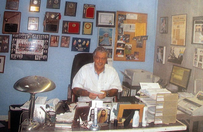 Richard Ferretti, Sr. at his desk at Hoppe's with his many community service awards on the wall.