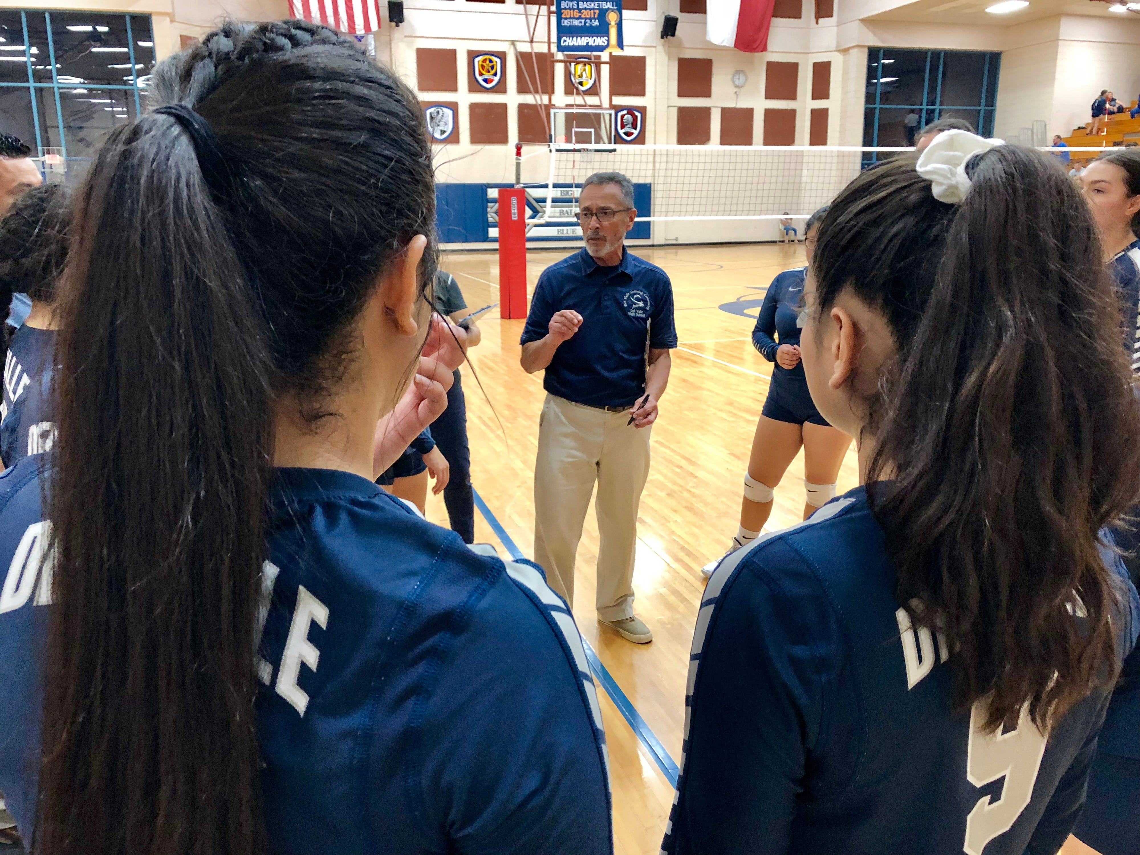 Del Valle coach Jesse Lugo meets with his team after they lost their first set against El Dorado Tuesday night.