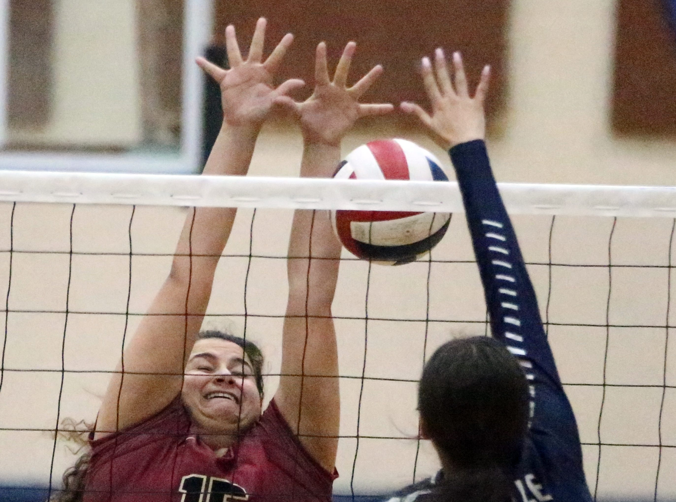Marissa Tovar, 5, of Del Valle manages to get the ball over the net despite the efforts of El Dorado's Jacueline Paz, 15, Tuesday night.