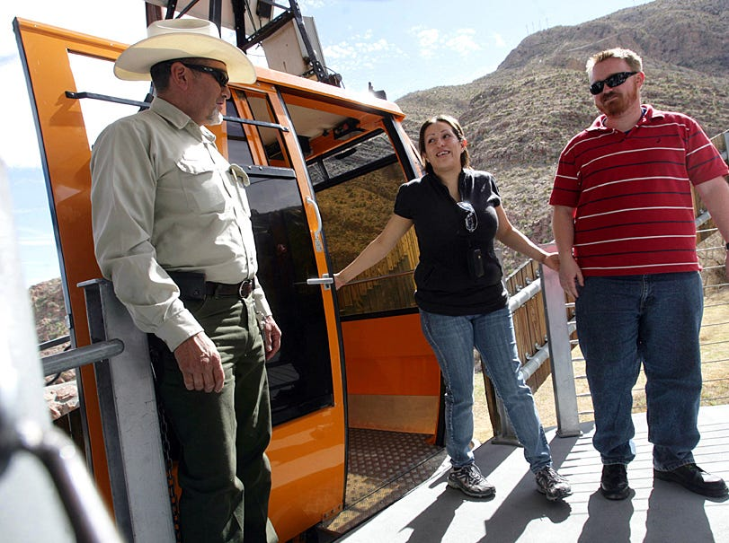 James Brown and Imelda Lopez deboard the Wyler Aerial Tramway Thursday after their ride down with Ranger Ismael Vela. Mark Lambie/El Paso Times