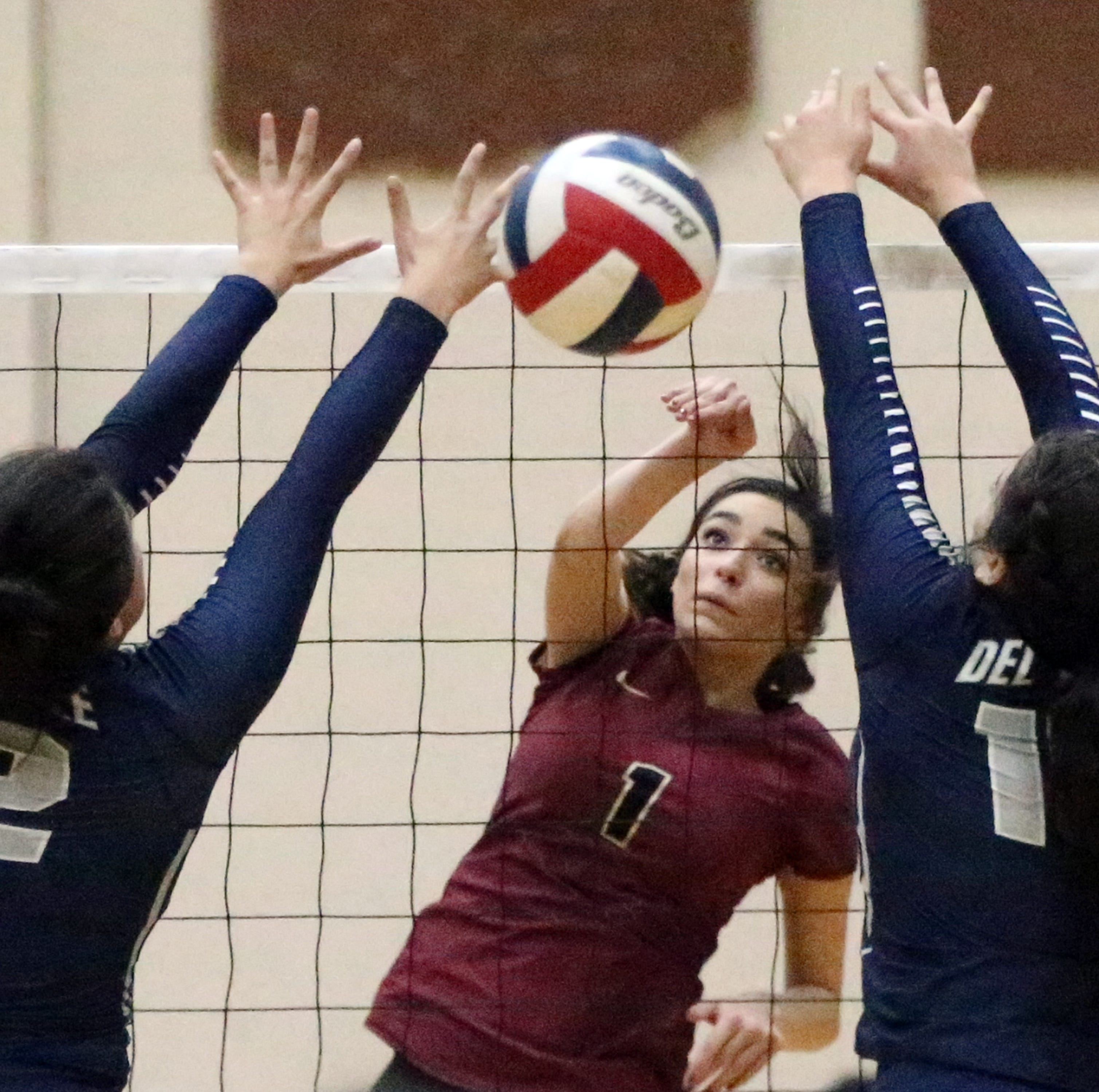Paig Mcgriff, 1, of El Dorado fires past Del Valle's Madison Valverde, 12, and Natalie Murillo, 15, Tuesday night at Del Valle. El Dorado won the match in three sets.