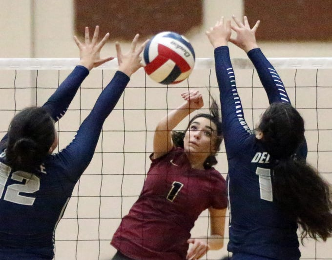 Paige McGriff, 1, of El Dorado fires past Del Valle's Madison Valverde, 12, and Natalie Murillo, 15, on Tuesday night at Del Valle. El Dorado won the match in three sets.