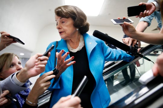 Sen. Dianne Feinstein, D-Calif., is surrounded by reporters as she arrives for a vote Tuesday on Capitol Hill in Washington.