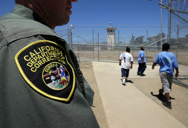 In this  June 20, 2018, file photo, inmates pass a correctional officer as they leave an exercise yard at the California Medical Facility in Vacaville.