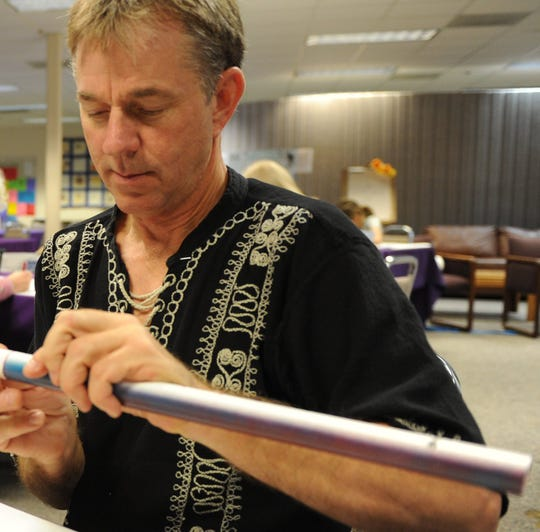 Flutes Across The World Director John Zeretzke places a cork into a flute during a Flutes Across the World class in Ventura in 2012.