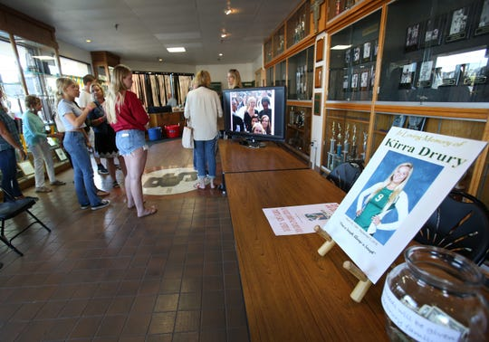Family and friends watch a memorial video that was set up at the entrance of St. Bonaventure High School gym in honor of Kirra Drury on Tuesday. A former star volleyball player at St. Bonaventure, Drury died in a boating accident on Sept. 1. The school remembered he before a match against Foothill Tech.