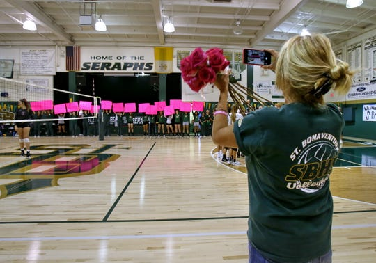 "Denise Olson Drury takes a photo of the St. Bonaventure JV girls volleyball team holding up cards that say ""We Love You Kirra"" to honor her daughter before the start of the varsity game Tuesday night at St. Bonaventure. Kirra Drury, who starred at St. Bonaventure, died in a boating accident Sept. 1."