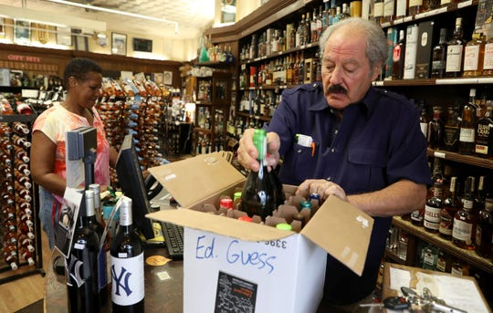 Tony Russo, owner of Aries Wine & Spirits in White Plains, packs a box of wine for customer Lorna Land. Russo is among those worried that the Total Wine franchise moving into Greenburgh will hurt his business.