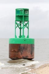 A buoy from the Delaware Bay sits on the beach south of the Woodland Beach fishing pier.