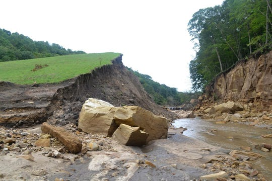 The earthen dam once 50 feet tall has a channel ripped through it after flood waters breached the dam, sending a wall of water down the valley, washing away everything in its path.
