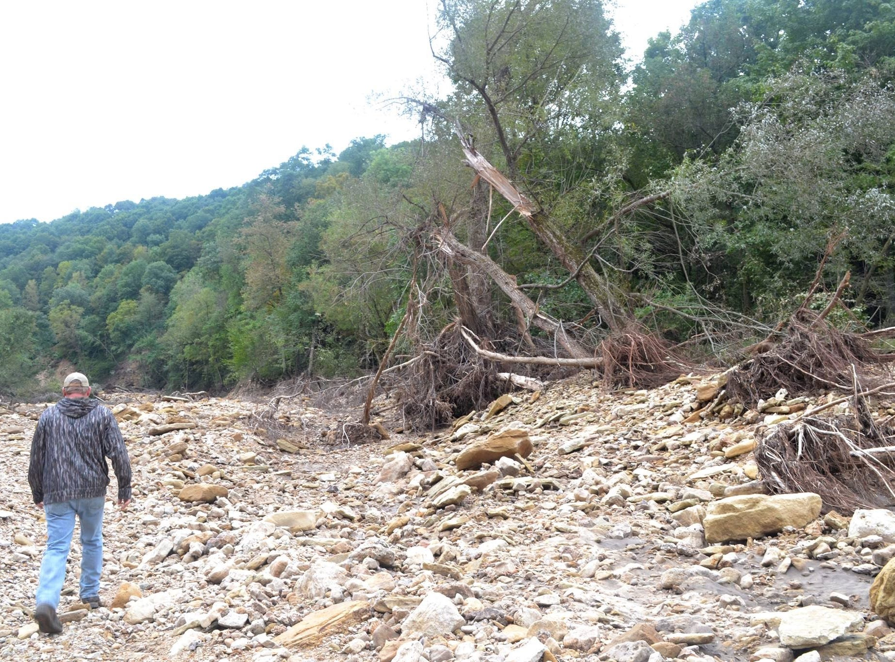 Miles of debris in the wake of the earthen dam breach litter the once verdant valley.
