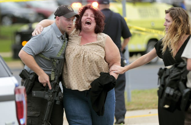A women is escorted from the scene of a shooting at a software company in Middleton, Wis., Wednesday, Sept. 19, 2018. Four people were shot and wounded during the shooting in the suburb of Madison, according to a city administrator.