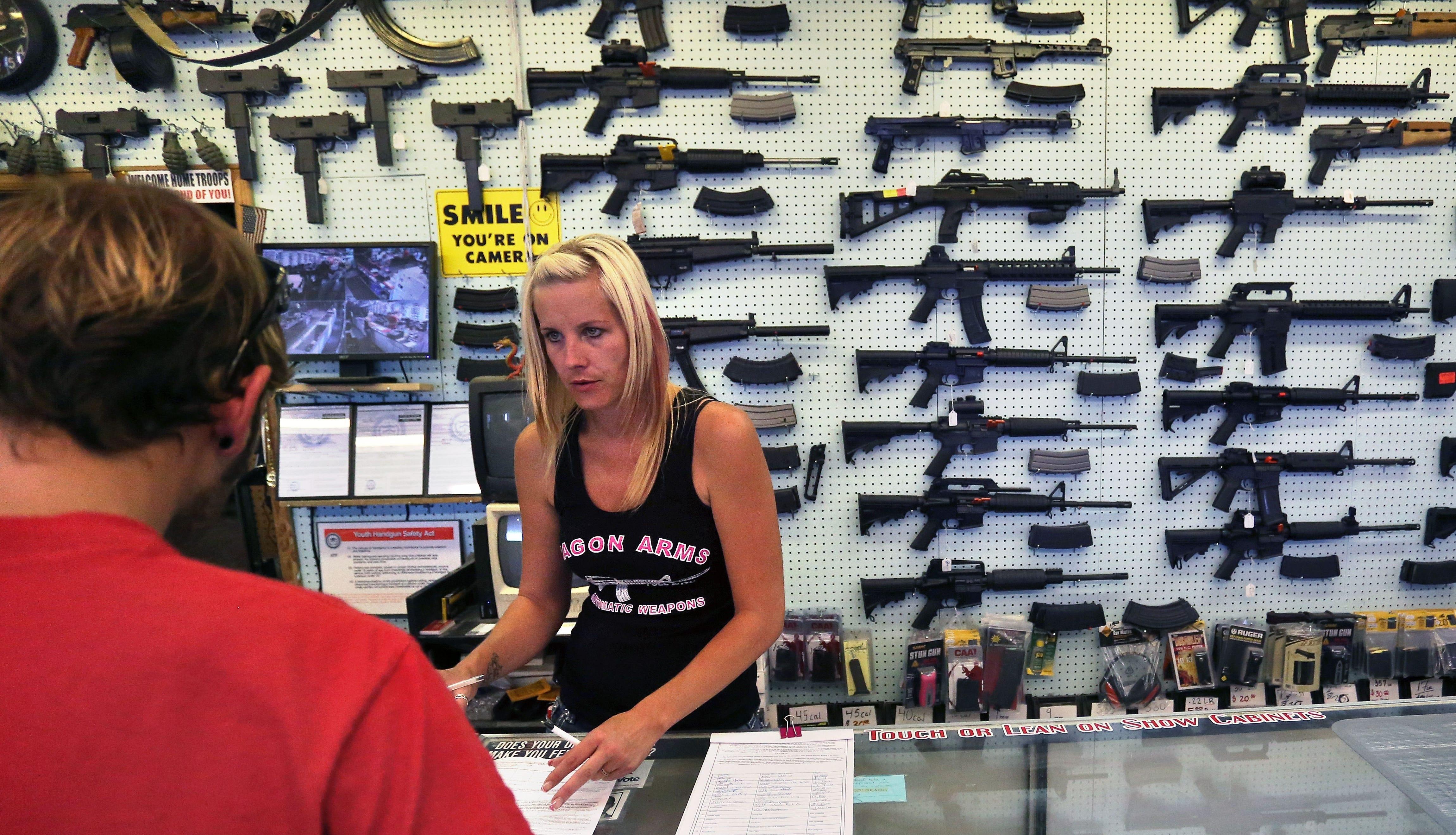 A gun store employee helps a customer near Colorado Springs, Colorado, in 2014.