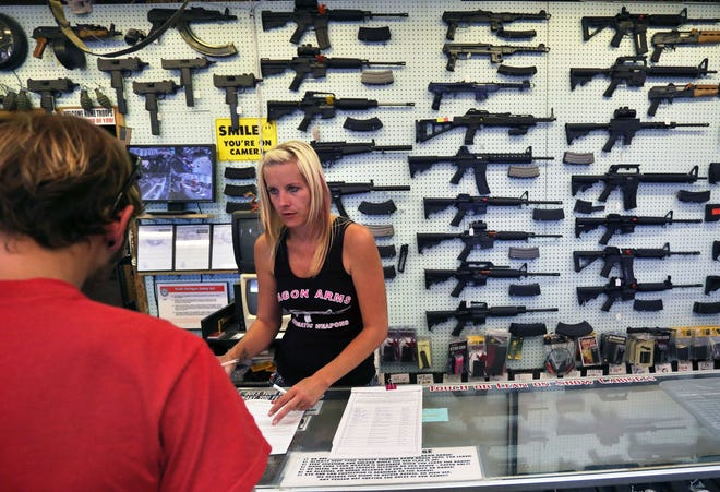 A gun store employee helps a customer near Colorado Springs, Colorado, in 2014.