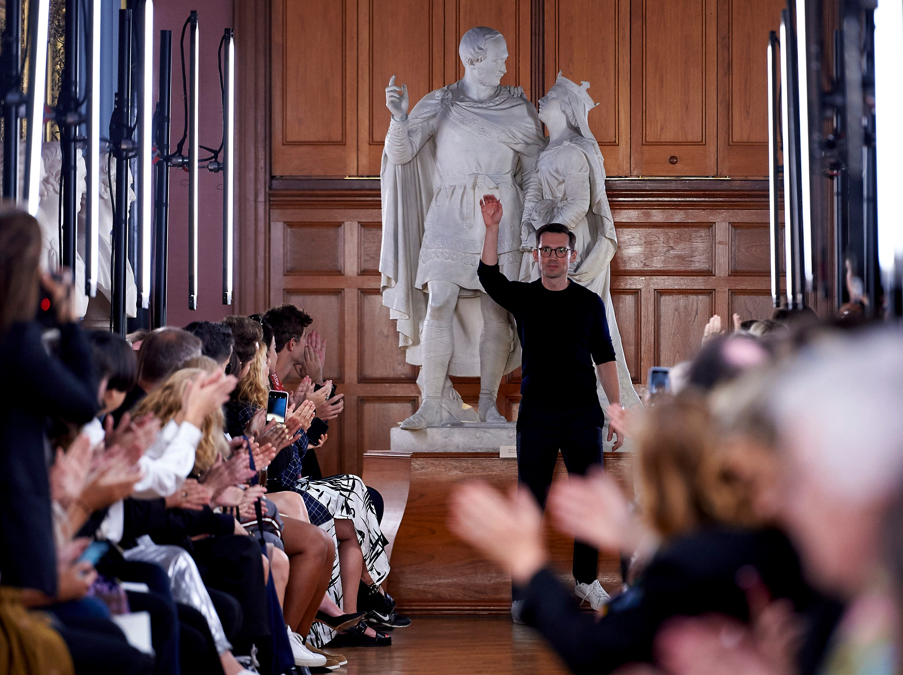 Turkish-Canadian designer Erdem Moralioglu receives applause after presenting his creations during a catwalk show for the Spring/Summer 2019 collection on the fourth day of London Fashion Week in London on September 17, 2018.