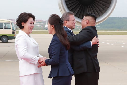 North Korean leader Kim Jong Un, right, and his wife Ri Sol Ju (2nd L) welcoming South Korean President Moon Jae-in (2nd R) and his wife Kim Jung-sook (L) during a ceremony at Pyongyang airport.