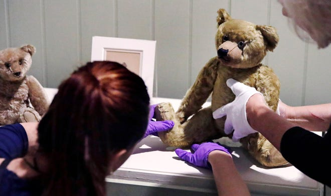 """Gallery stylists at Boston's Museum of Fine Arts position antique Winnie the Pooh bears in advance of Saturday's opening of  the """"Winnie-the-Pooh: Exploring a Classic"""" exhibit."""
