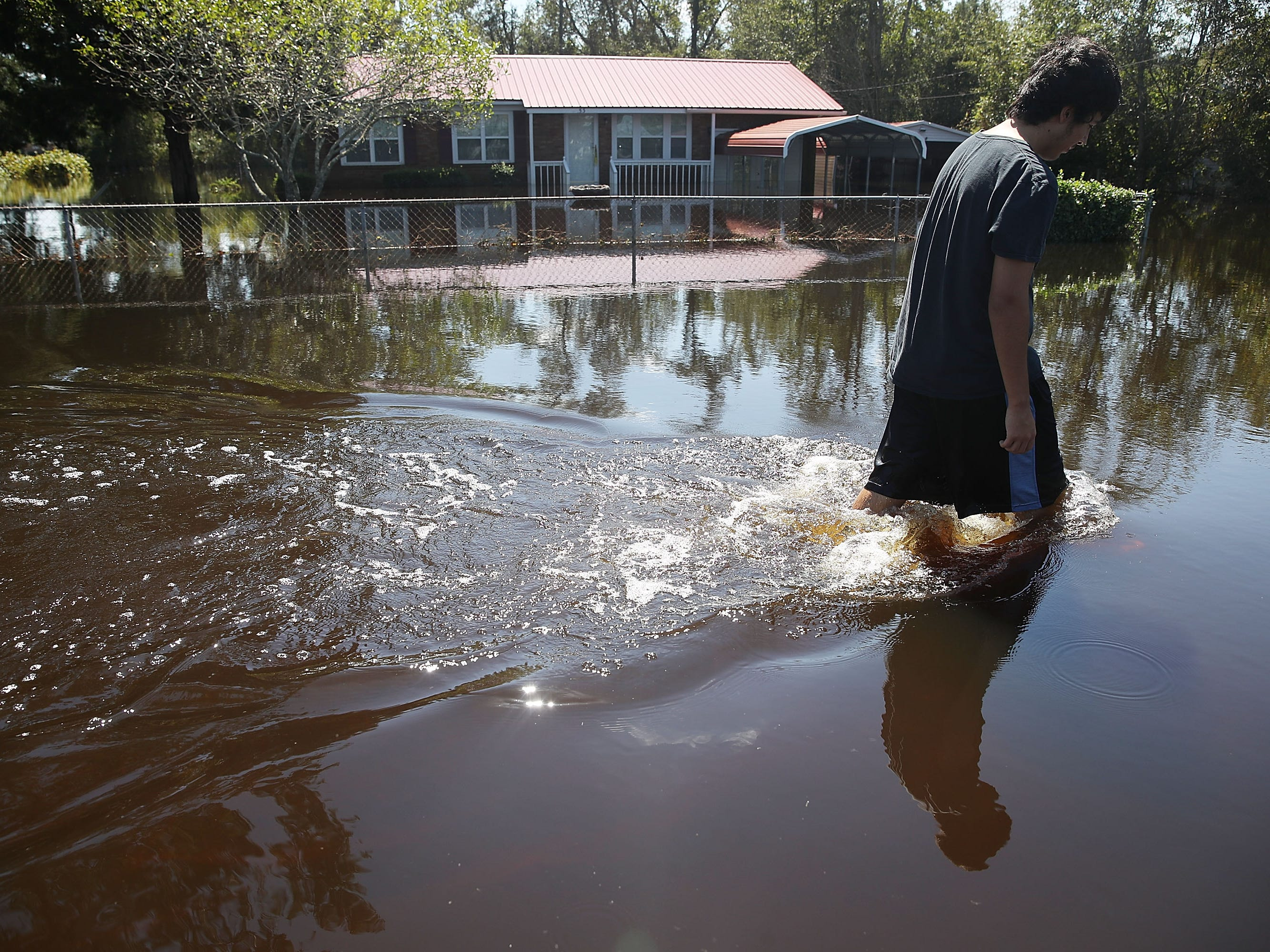 Jovani Quintano walks through a flooded neighborhood after heavy rains brought on by Hurricane Florence on Sept. 19, 2018, in Lumberton, N.C.