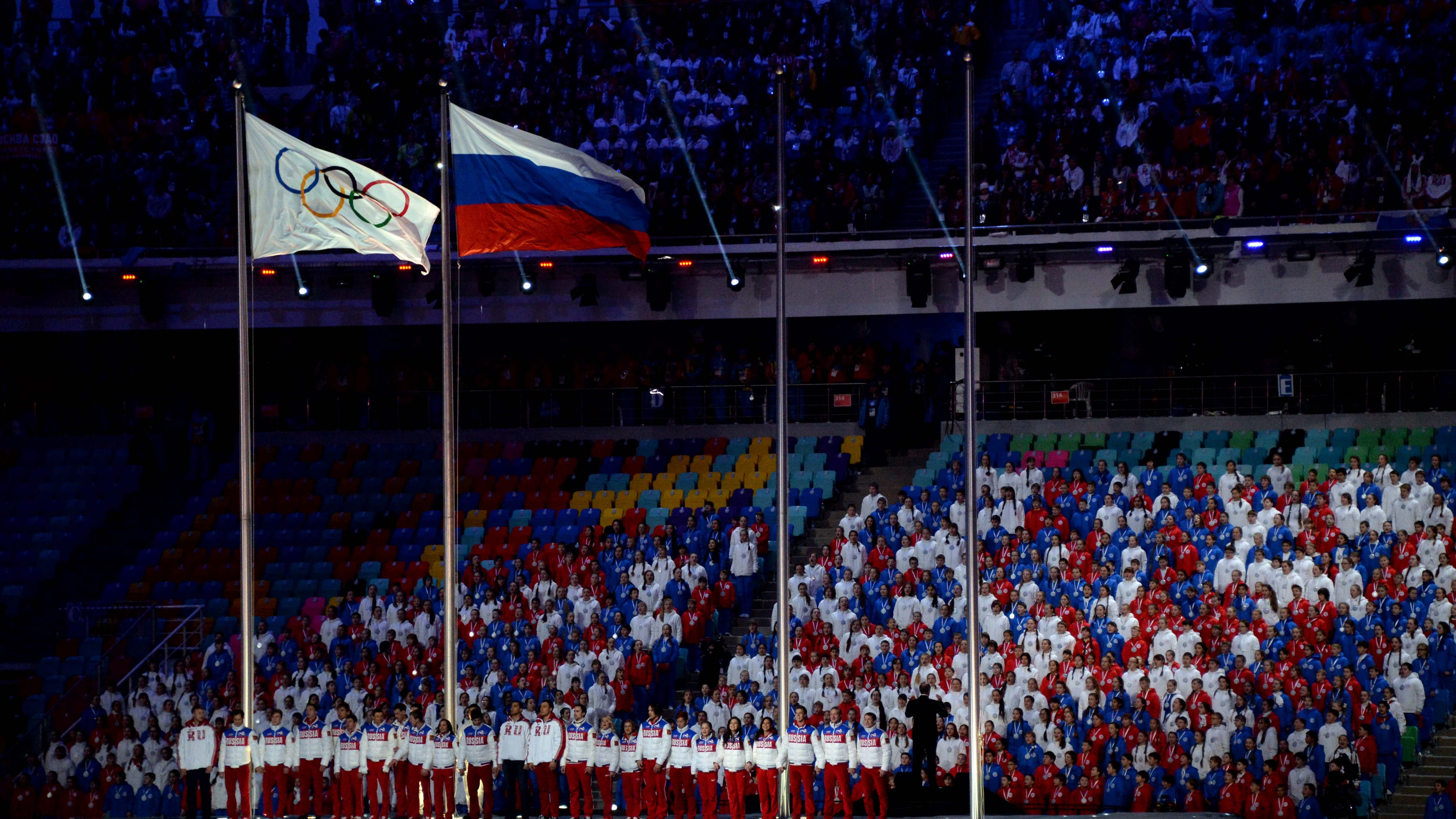 Russian gold medalists are seen on stage as the flag is raised next to the Olympic flag during the closing ceremony for the Sochi 2014 Olympic Winter Games.
