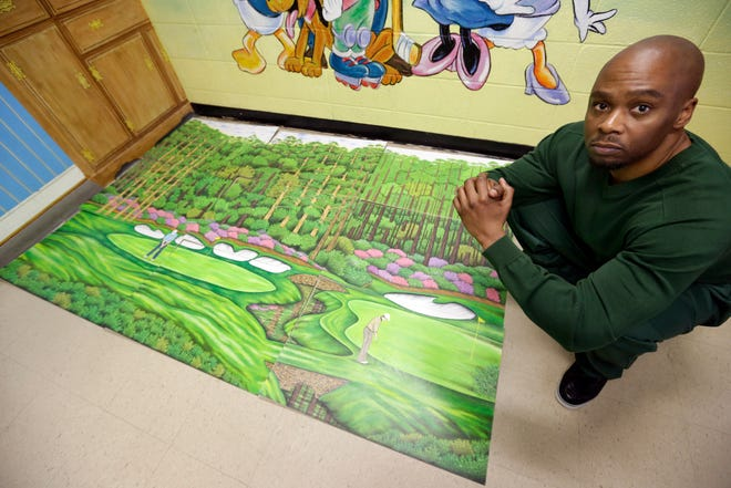 In a May 2013 file photo, Attica (N.Y.) Correctional Facility inmate Valentino Dixon poses with one of his golf drawings he created while in prison.