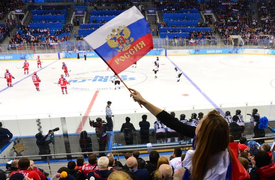 A fan waves a Russian flag at a women's hockey game between Russia and Japan during the Sochi 2014 Olympic Winter Games.