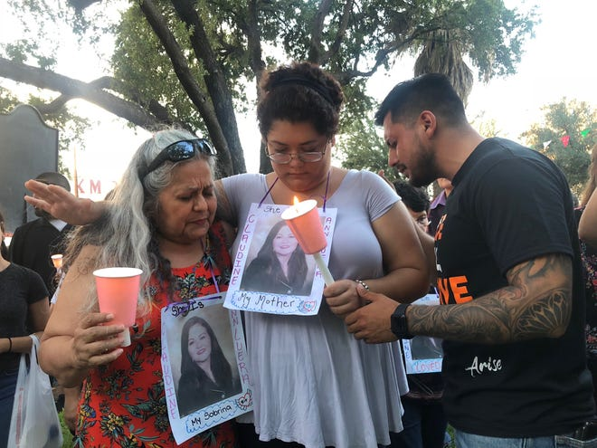 Members of the family of Claudine Ann Luera pray at a candlelight vigil for victims in Laredo's San Agustin Plaza on Tuesday, Sept. 18. Police said Luera was the second victim allegedly killed by U.S. Border Patrol agent Juan David Ortiz, on Sept. 13.