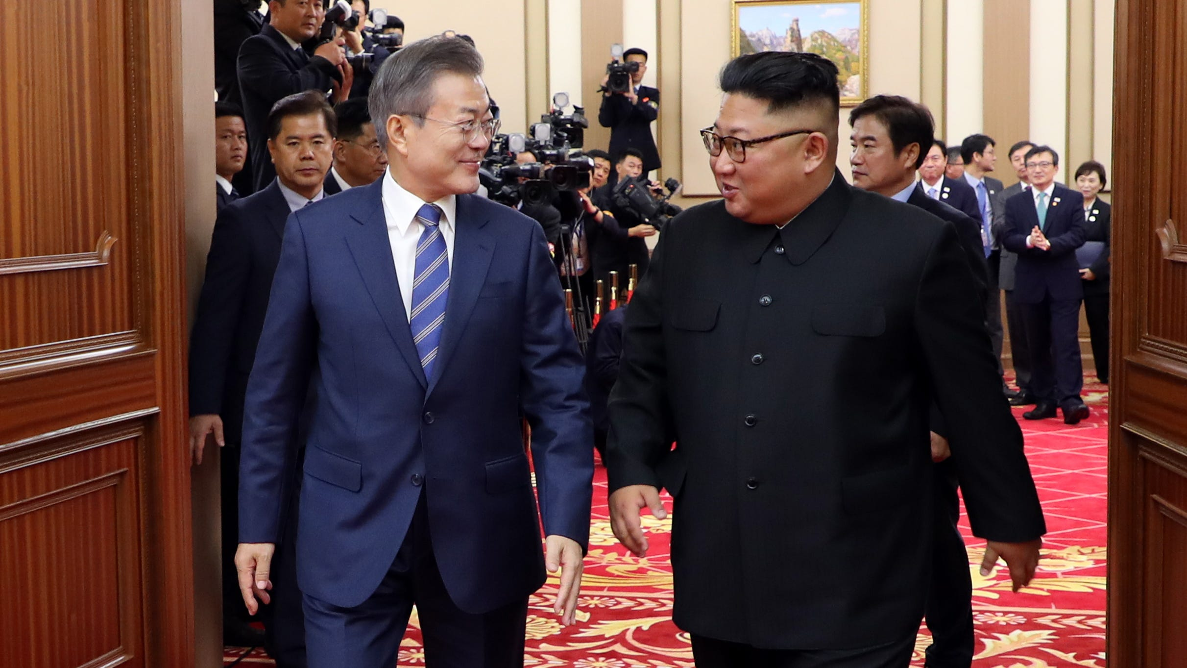 South Korean president Moon Jae-in (L) talks with North Korean leader Kim Jong Un as they leave after a press conference in Pyongyang, North Korea, 19 September 2018.