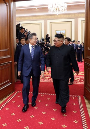 South Korean President Moon Jae-in, left, talks with North Korean leader Kim Jong Un as they leave a press conference in Pyongyang, North Korea, on Sept. 19, 2018.