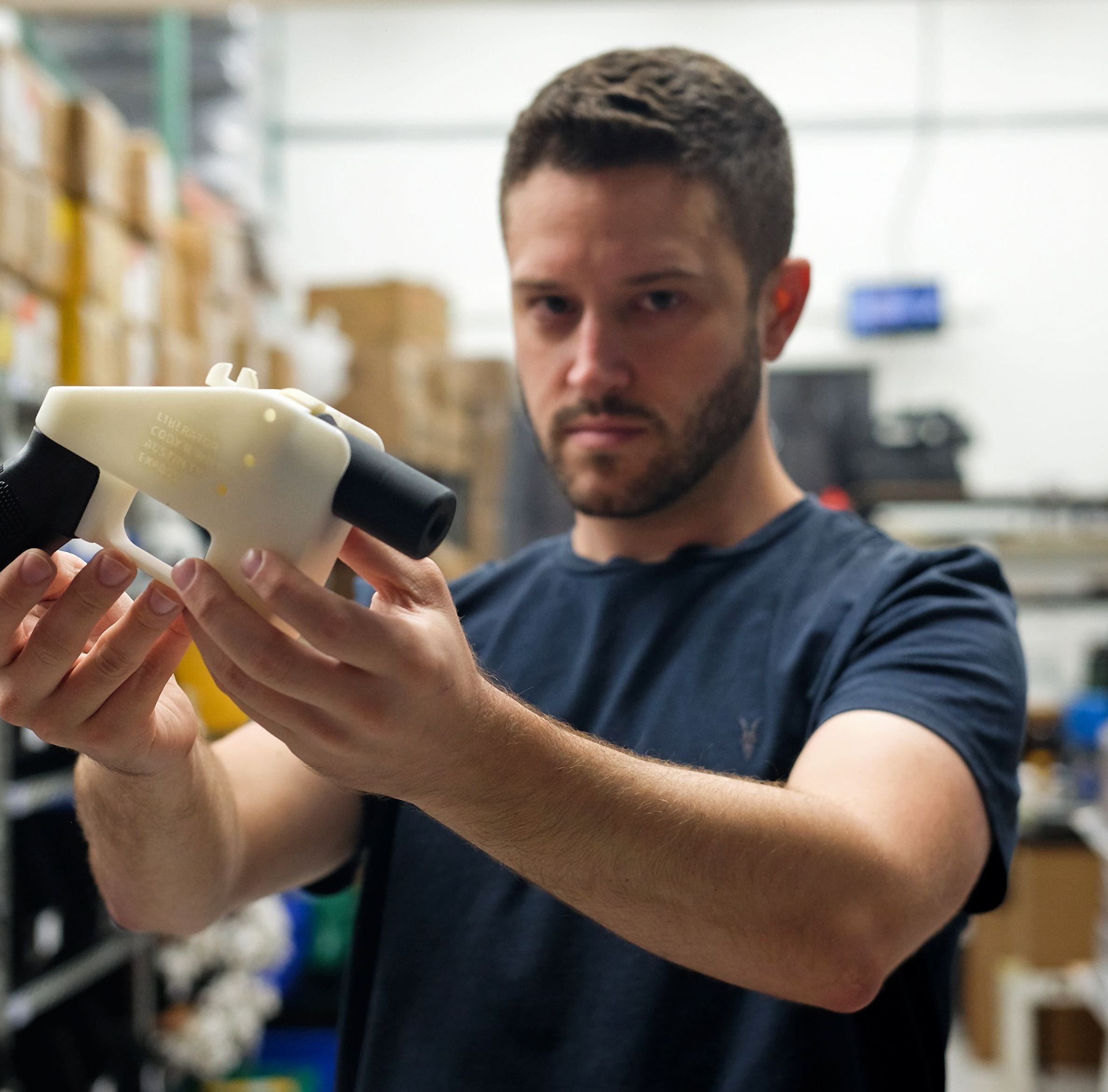 "Cody Wilson, owner of Defense Distributed company, holds a 3D printed gun, called the ""Liberator,"" in his factory in Austin, Texas on August 1, 2018."