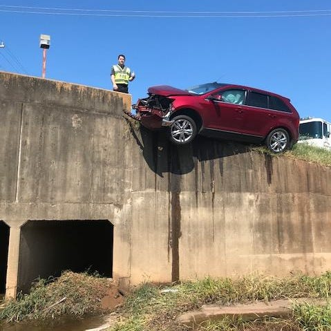 Nobody injured after car hits abutment, teeters on edge