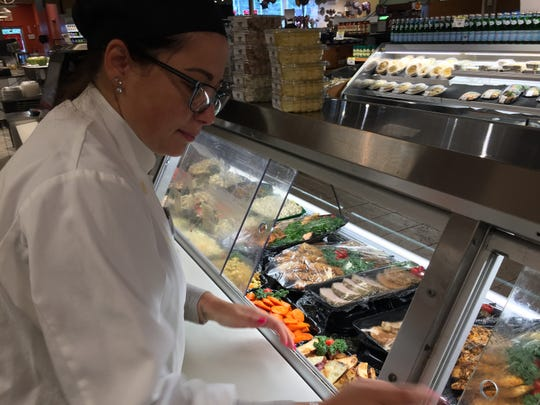 Marisa Marques, kitchen manager for Super Foodtown in Ocean Township, prepares the counter.