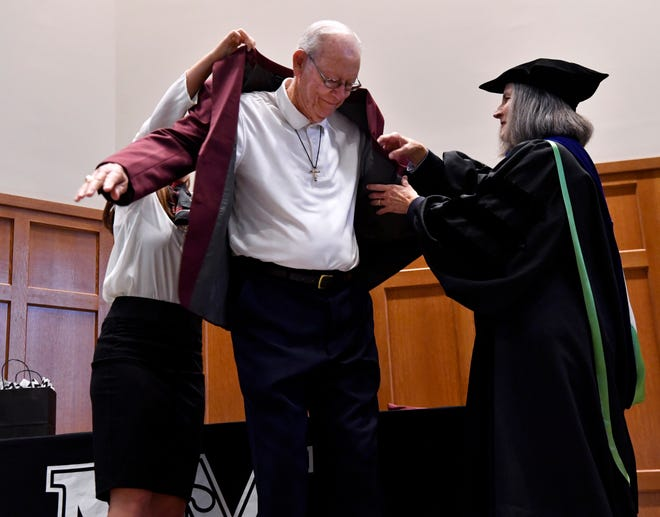 McMurry University President Sandra Harper assists Don Taylor with the maroon sport coat he was awarded Thursday before convocation. Fifteen former McMurry students were given coats and named as Trailblazers.
