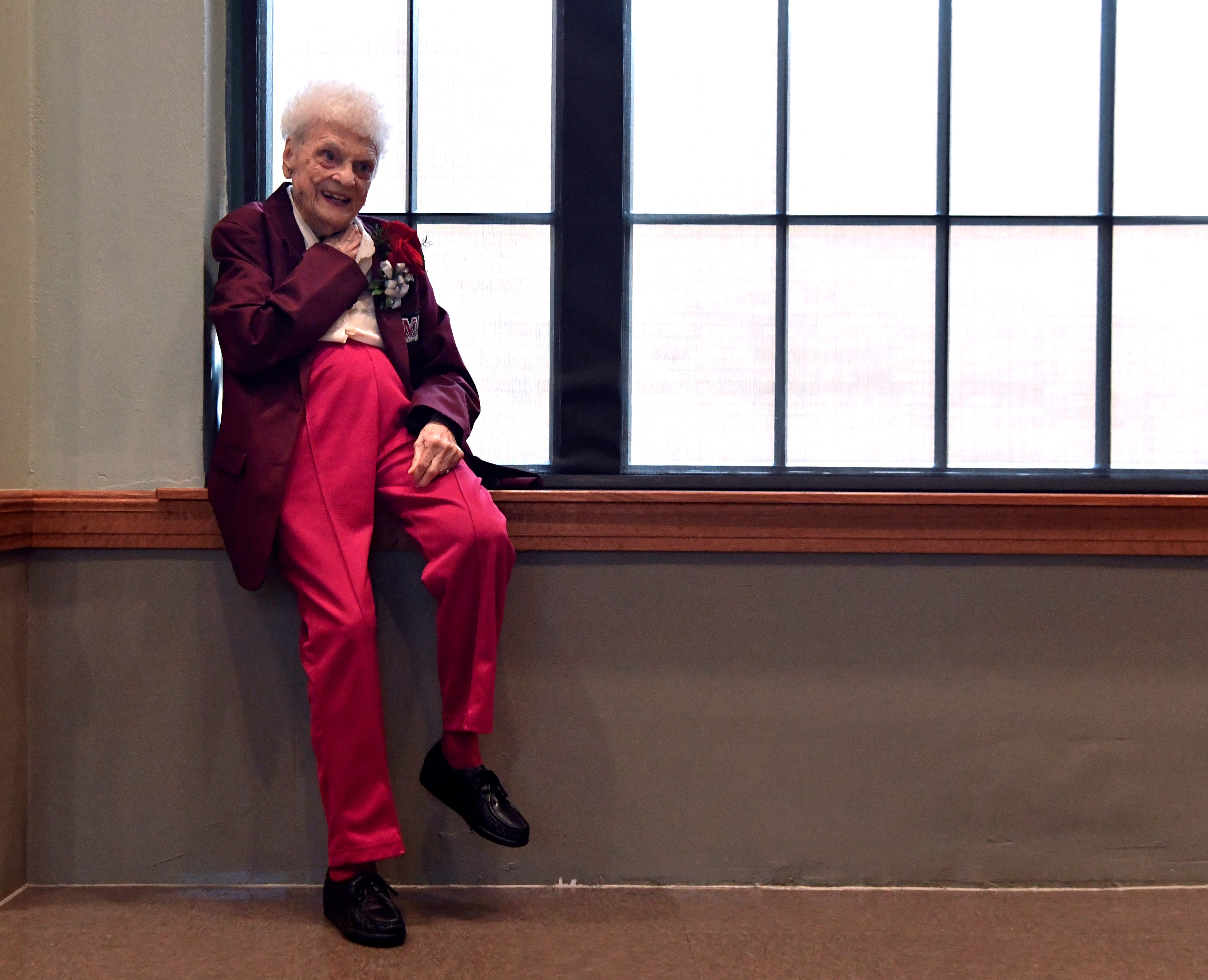 "Frances Hill Cooper ""Weeze"" Daniel relaxes on a window sill beside the stage in Matthews Auditorium at McMurry University Thursday wearing her new maroon blazer. The coat designates the 1938 graduate, along with 14 other alumni in the ceremony, as McMurry Trailblazers."