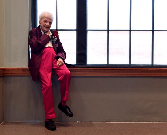 """Frances Hill Cooper """"Weeze"""" Daniel relaxes on a window sill beside the stage in Matthews Auditorium at McMurry University Thursday wearing her new maroon blazer. The coat designates the 1938 graduate, along with 14 other alumni in the ceremony, as McMurry Trailblazers."""