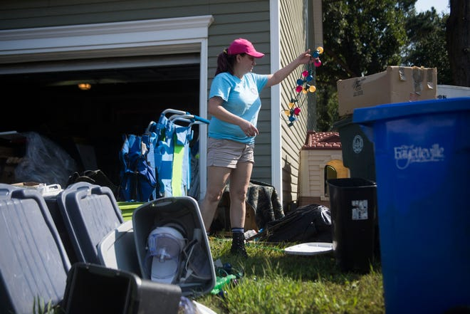 A Cedar Creek neighborhood resident throws out flood damaged belongings in Fayetteville, N.C., Thursday, Sept. 20, 2018. This is the second time her house has flooded in two years.