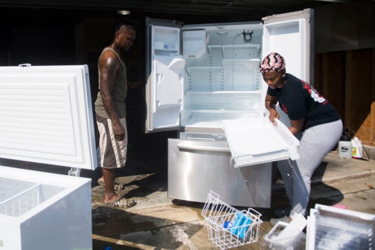 Mike Dougal and Jasmine Brown clean out their flooded freezer and refrigerator outside their garage in the Cedar Creek neighborhood of Fayetteville, N.C., Thursday, Sept. 20, 2018.  This is the second time the house has flooded in two years. They plan to move out of the neighborhood, but fear the house's chance for resale may be ruined.