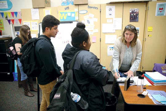 Bremerton High School AVID class teacher Lisa Gordon signs students up for meetings as class ends on Thursday. The AVID program lines students up with community mentors, who help them jump hurdles associated with the college admissions process.