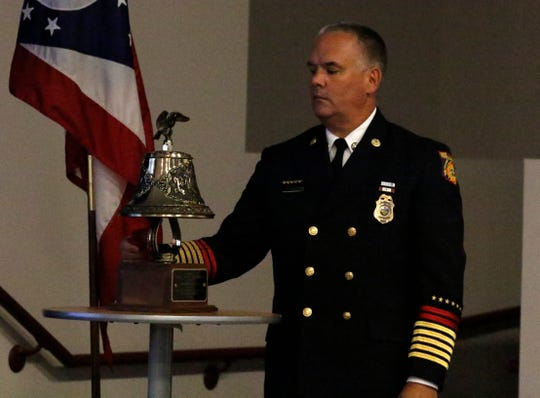 State Fire Marshal Jeff Hussey rings a bell honoring Joe Patterson and Rodney Baker Jr. during a ceremony to honor firefighters who died in the last year while on duty.