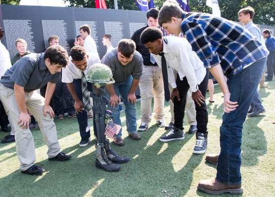Football players from Huntington High School visit the Traveling Vietnam Wall and look at the wall and Battlefield Cross placed in front of it. The students arrived to watch the ceremony and to help any veterans if needed.