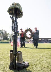 Tim Velarde and Thomas Estes walk towards the Traveling Vietnam Wall to lay a wreath close to the Battlefield Cross.