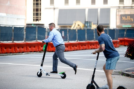 Two men ride scooters on Elm Street and Fourth Streets  Thursday, September 20, 2018.