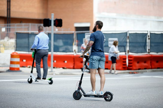 One man rides a Lime Scooter, left, while the other rides a Bird scooter on Elm Street Thursday, September 20, 2018.
