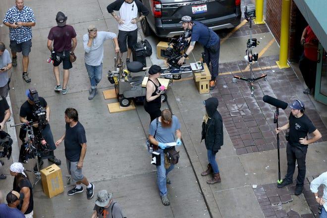 The crew and cast of 10 Minutes Gone in between scenes of filming in Benham Alley Thursday in Downtown Cincinnati.